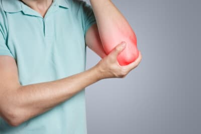Man feeling a pain in his elbow on grey background pain