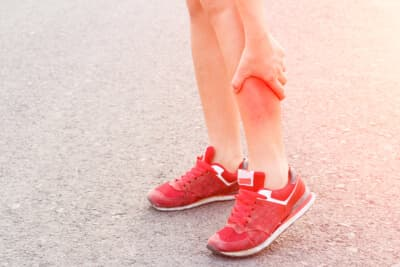 Woman runner leg and muscle pain on road in morning